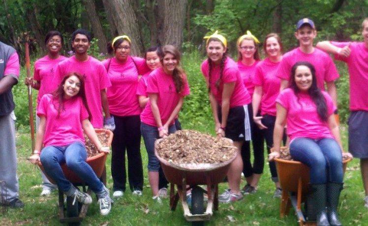 Group of volunteers posing with wheel barrels full of mulch